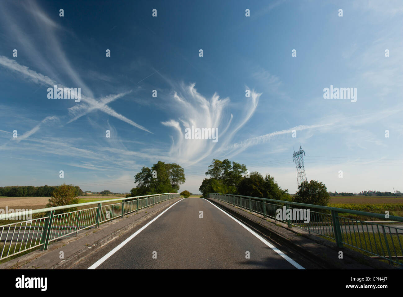 Whispy clouds and vapor trails in sky over bridge - Stock Image