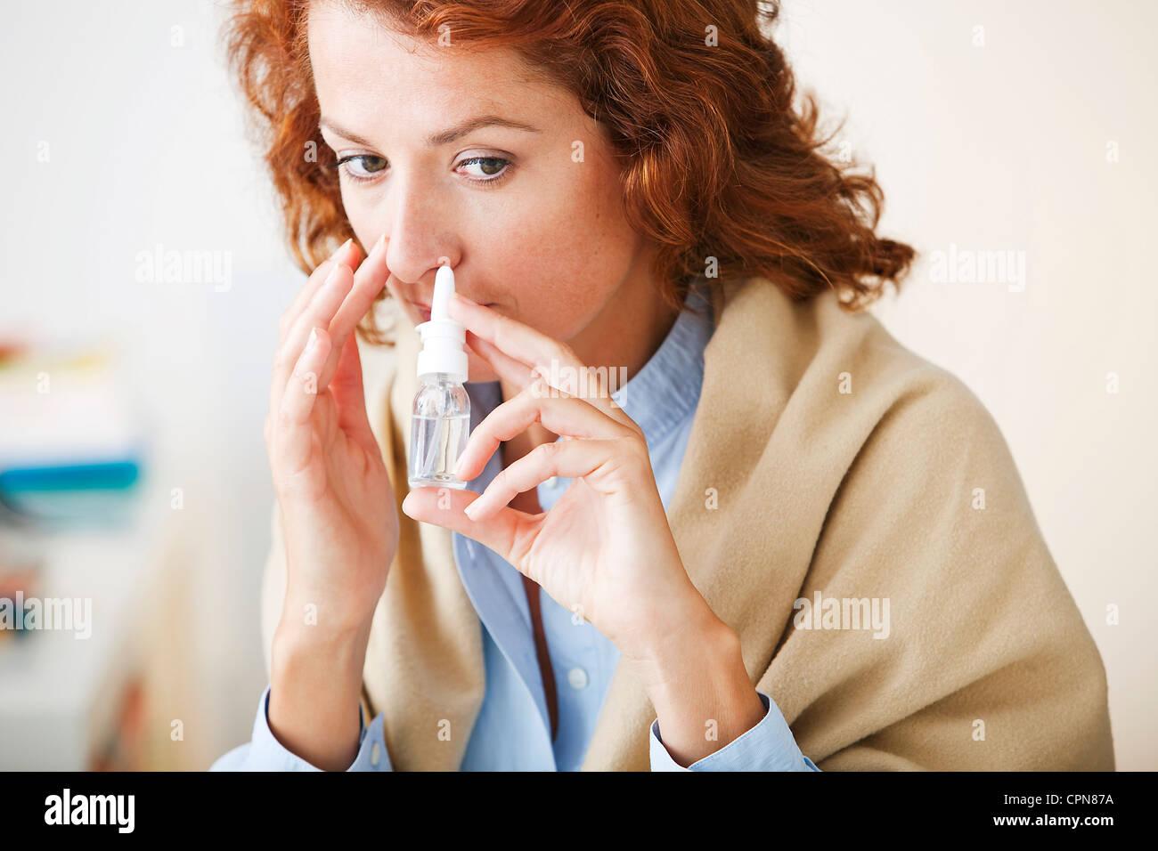 WOMAN USING NOSE SPRAY - Stock Image