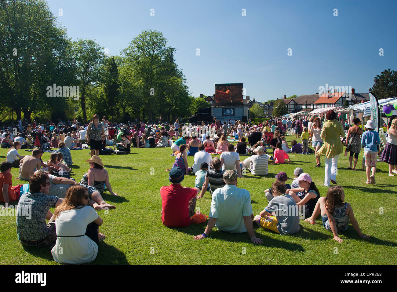 Families watching an open air mobile cinema in Hall Leys Park, Matlock, Derbyshire, England, UK, on a hot sunny - Stock Image