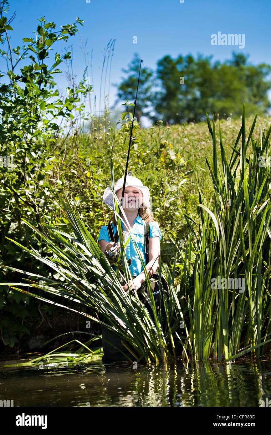 little girl fishing on lake at summer - Stock Image
