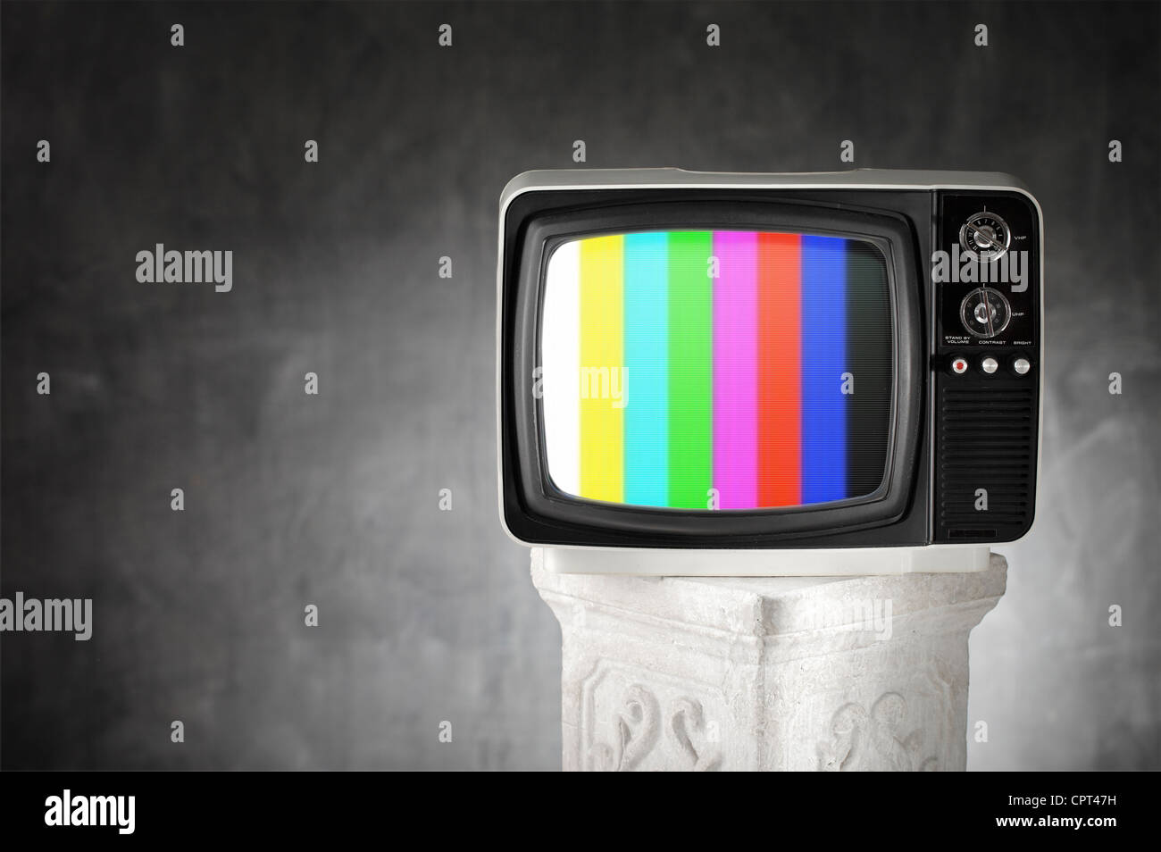 Old television with color bars on a plaster column. - Stock Image