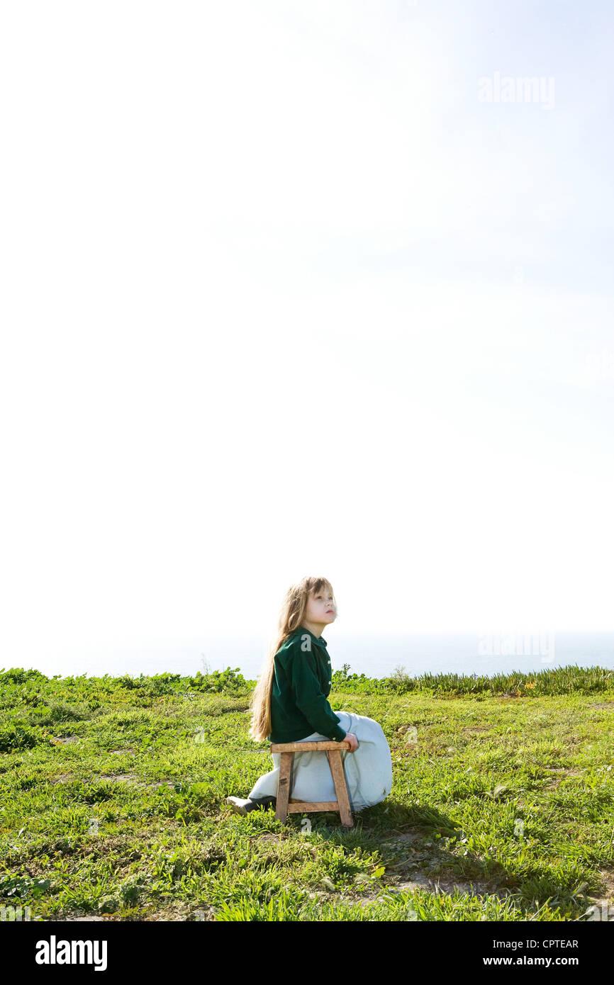 Girl sitting alone in field under bright sky - Stock Image