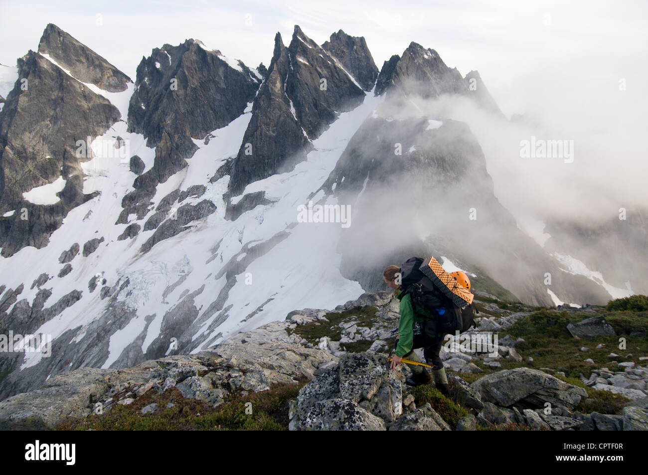 Female backpacker on ridge with fog, Picket Pass, North Cascades National Park, WA, USA - Stock Image