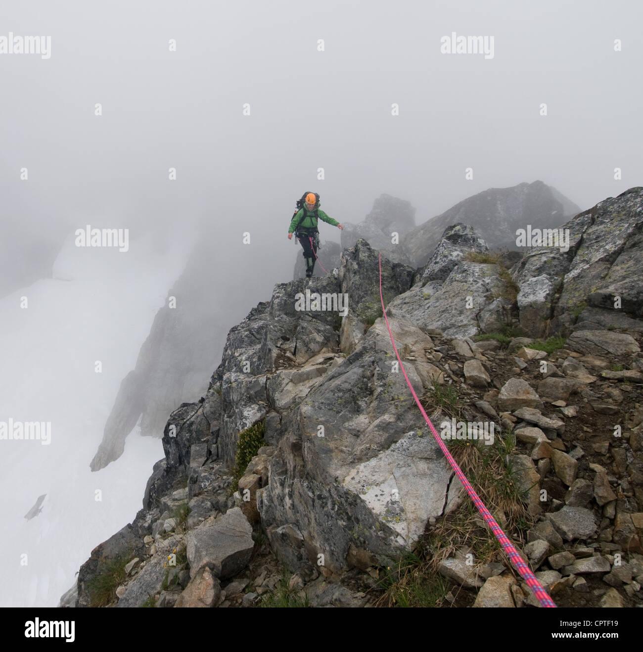 Female climber crossing rock ridge, Picket Pass, North Cascades National Park, WA, USA - Stock Image