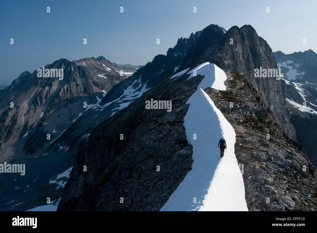 Female climber traversing snowy ridge, Redoubt Whatcom Traverse, North Cascades National Park, WA, USA - Stock Image