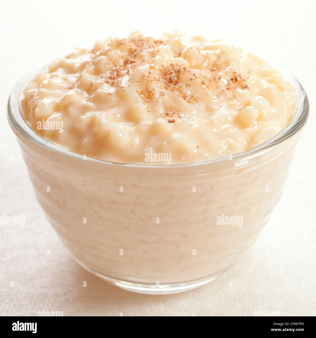 Rice pudding sprinkled with nutmeg in an individual glass bowl. Stock Photo