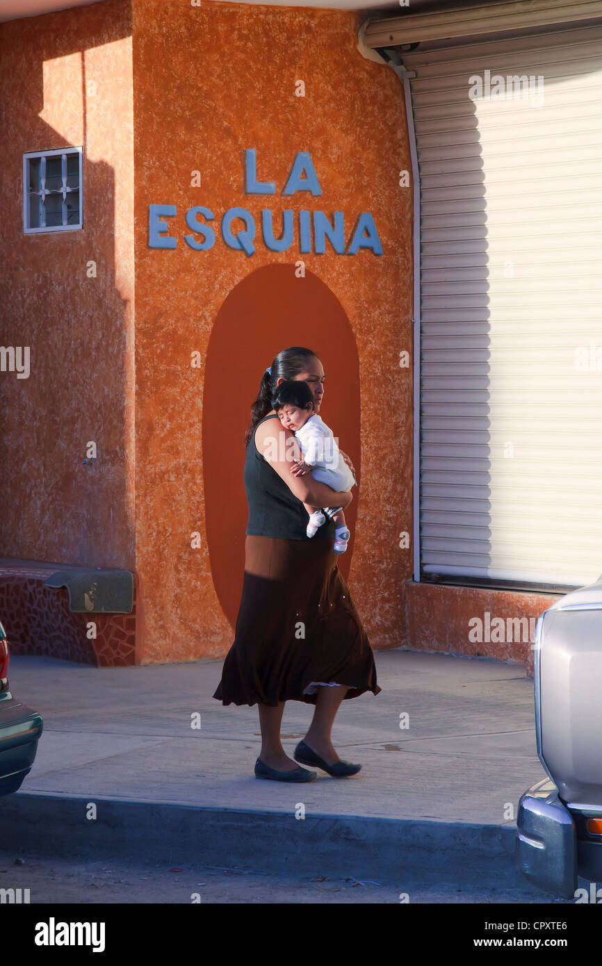 young-mexican-woman-carrying-a-sleeping-baby-in-her-arms-CPXTE6.jpg