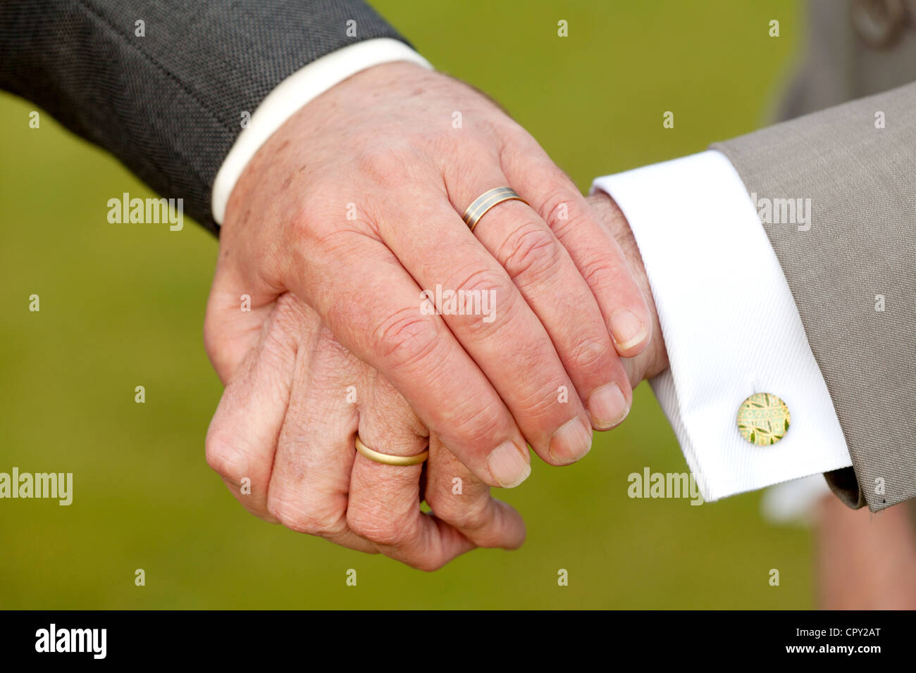 Two smartly dressed.homosexual, gay, men holding hands and showing off their wedding rings, after a civil registrar Stock Photo