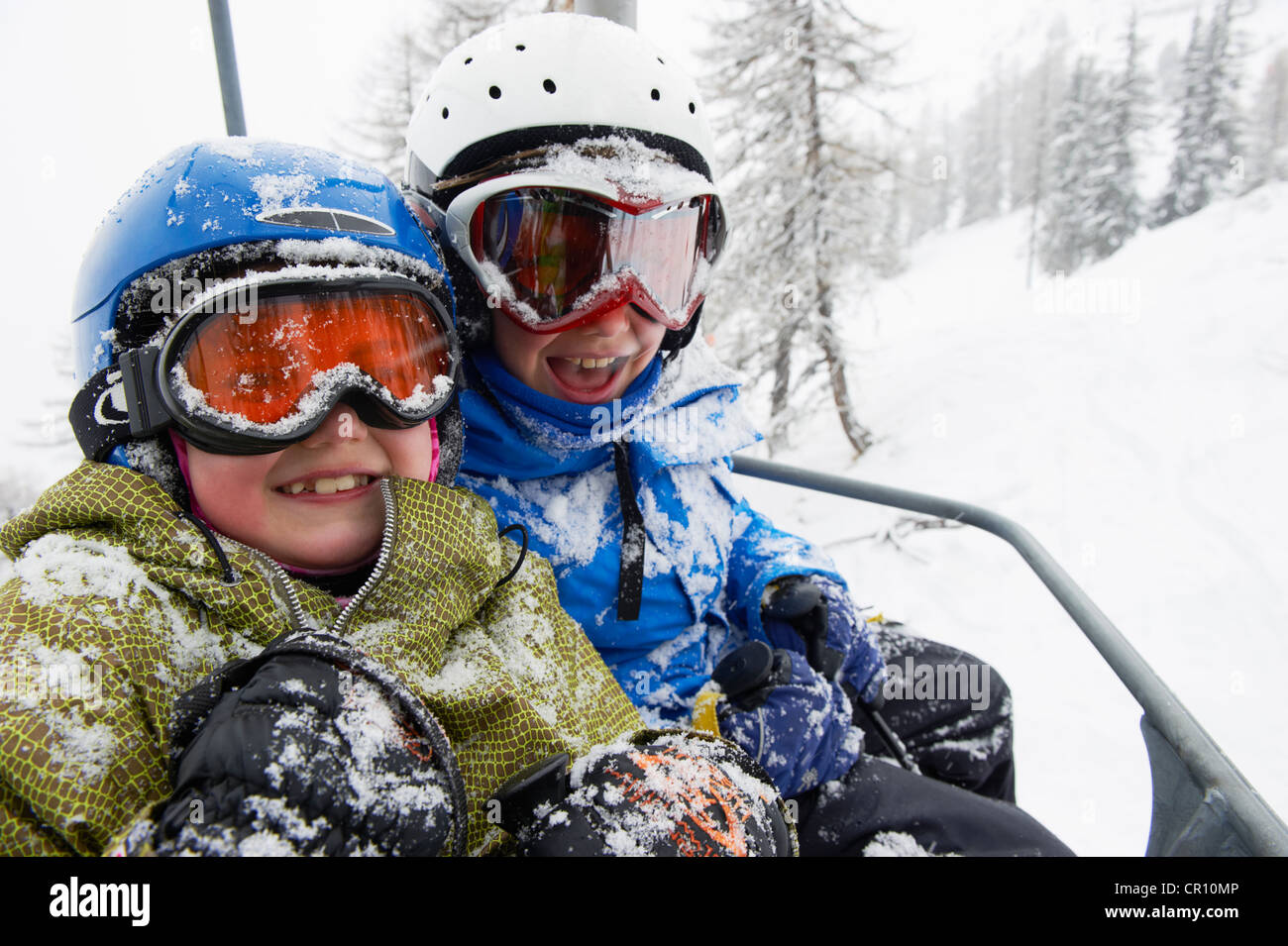 Snow-covered children in ski lift - Stock Image