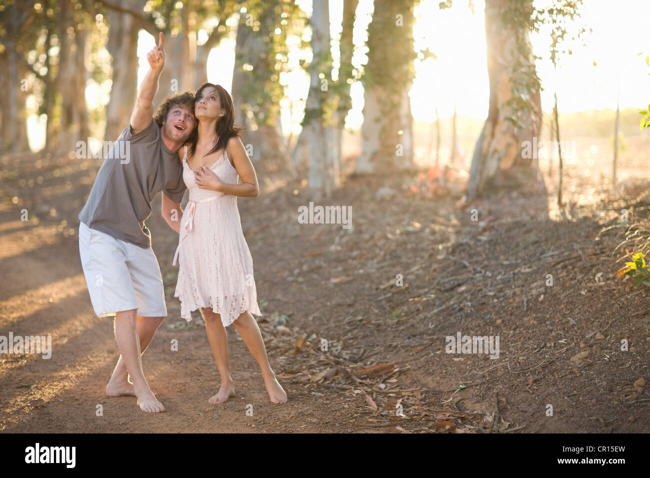 Couple walking together on dirt road - Stock Image