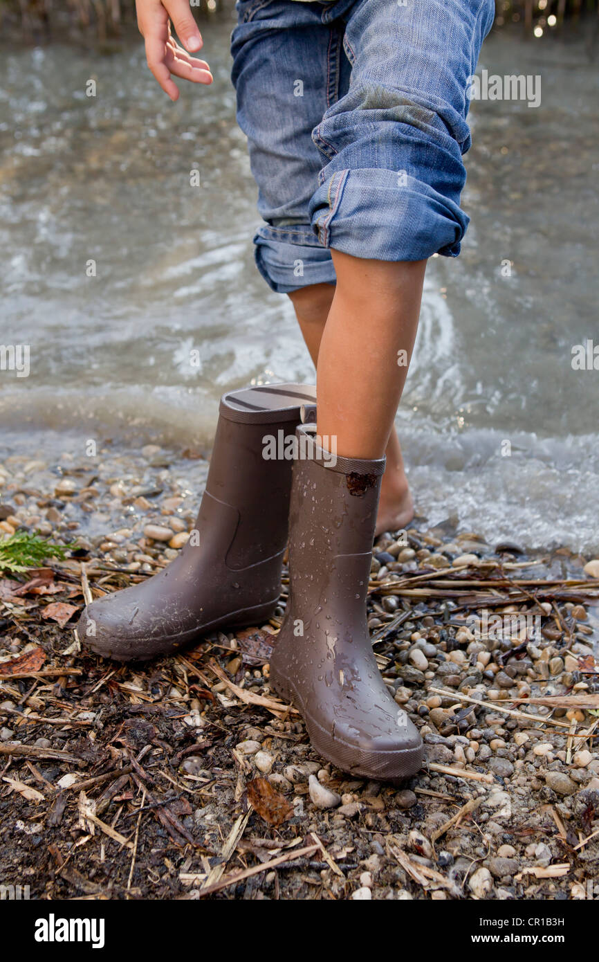 Girl taking off rain boots by pond - Stock Image