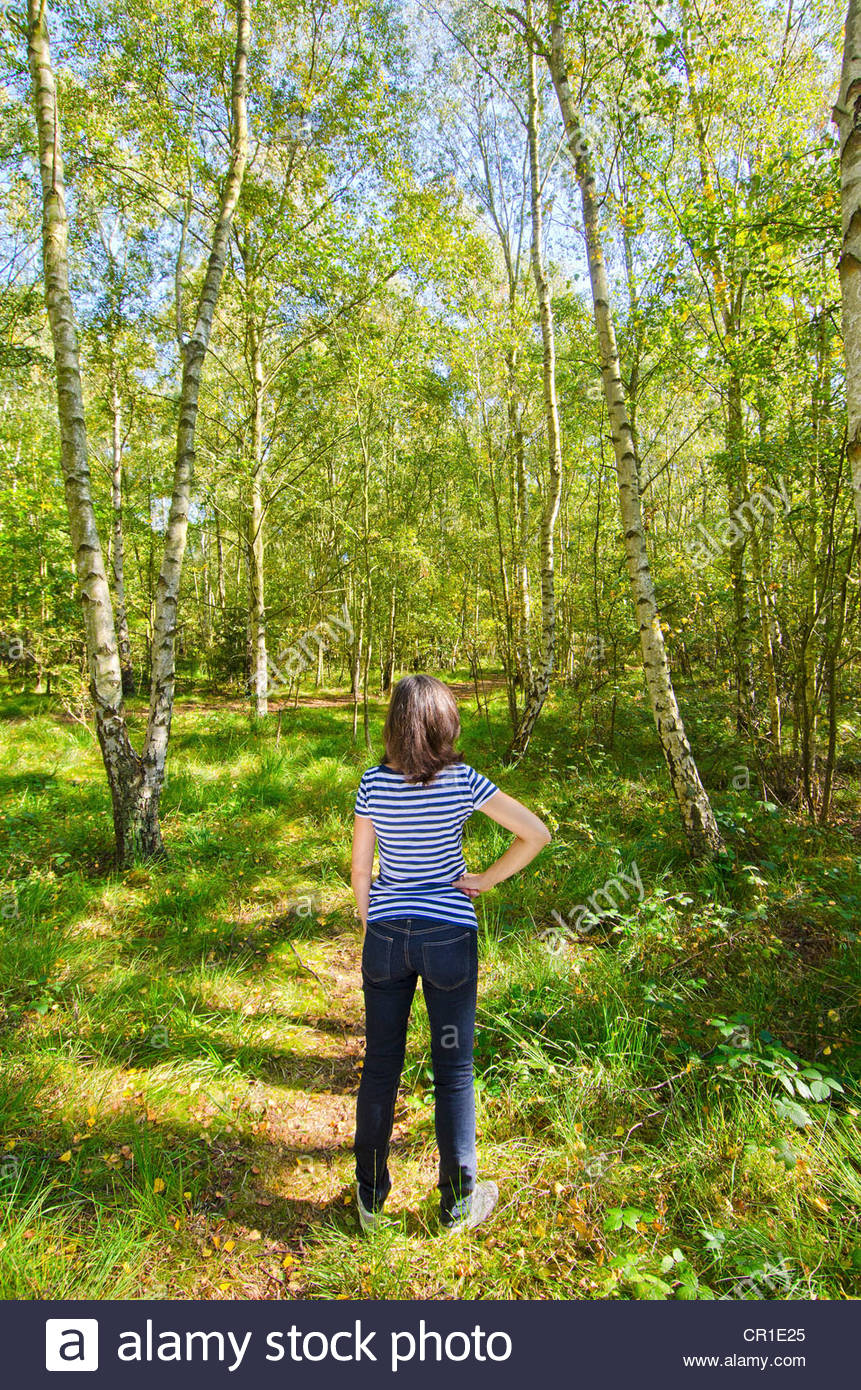 Older woman standing in forest - Stock Image