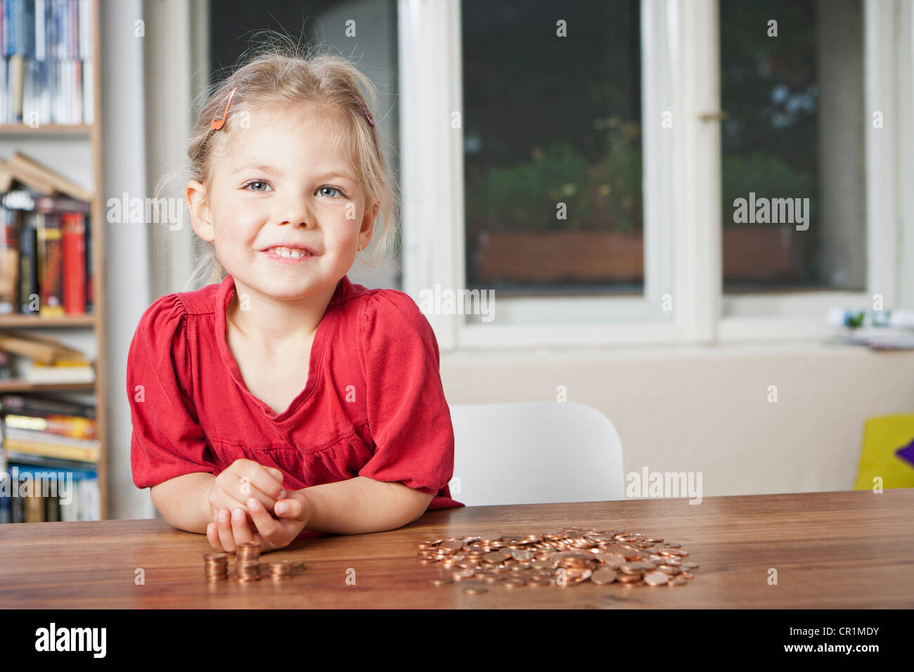 Girl playing with pennies at table - Stock Image