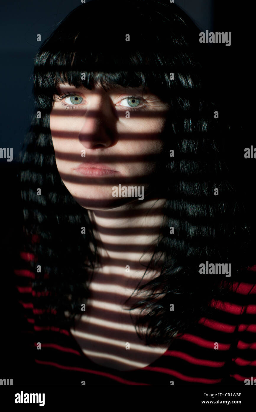 Woman standing in blinds shadow - Stock Image