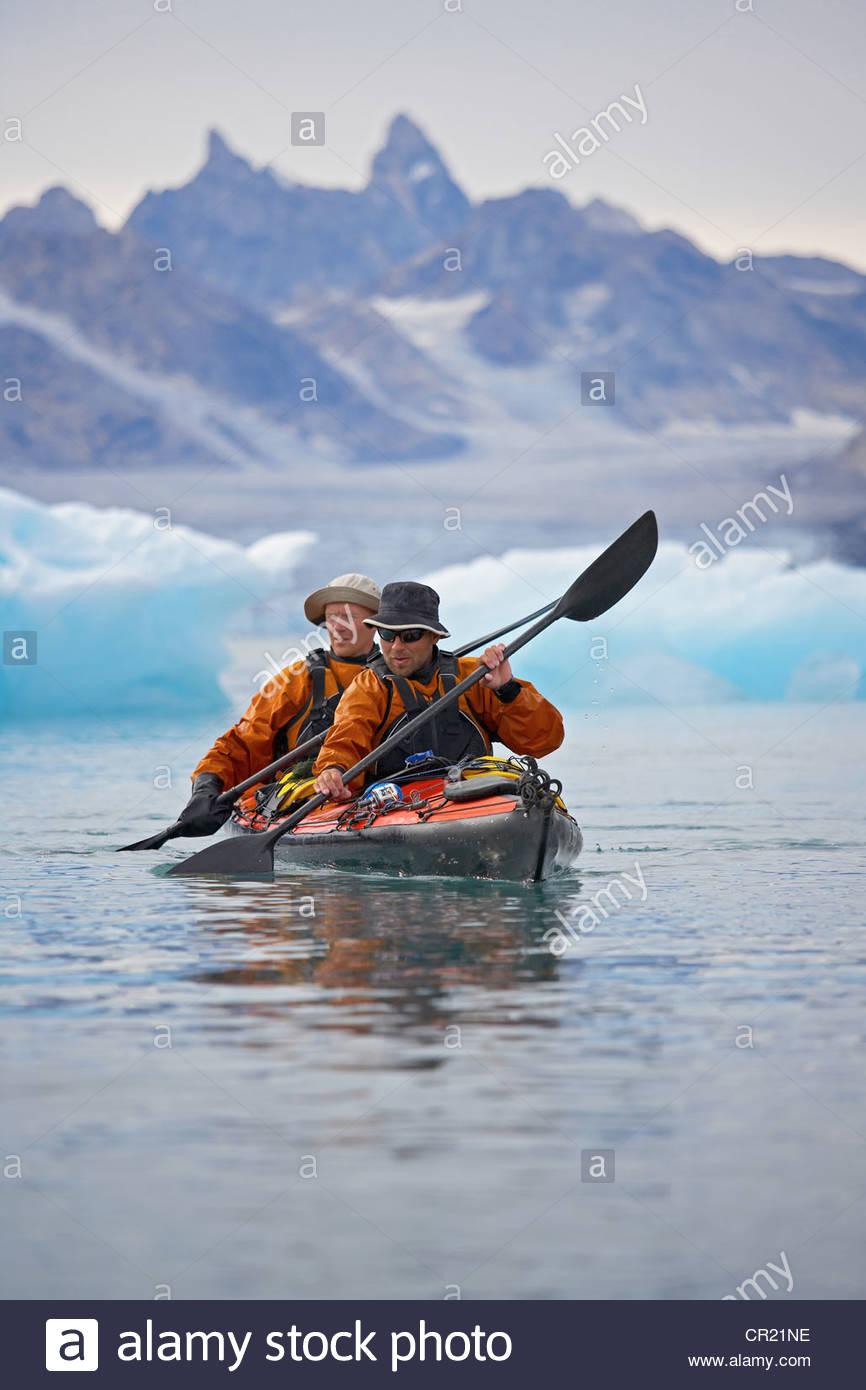 Men rowing canoe on still glacial sea - Stock Image