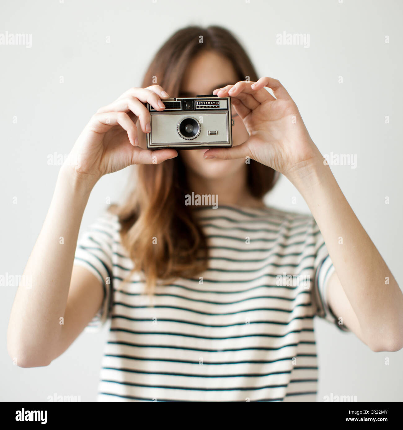 Studio shot of young woman with old-fashioned camera - Stock Image