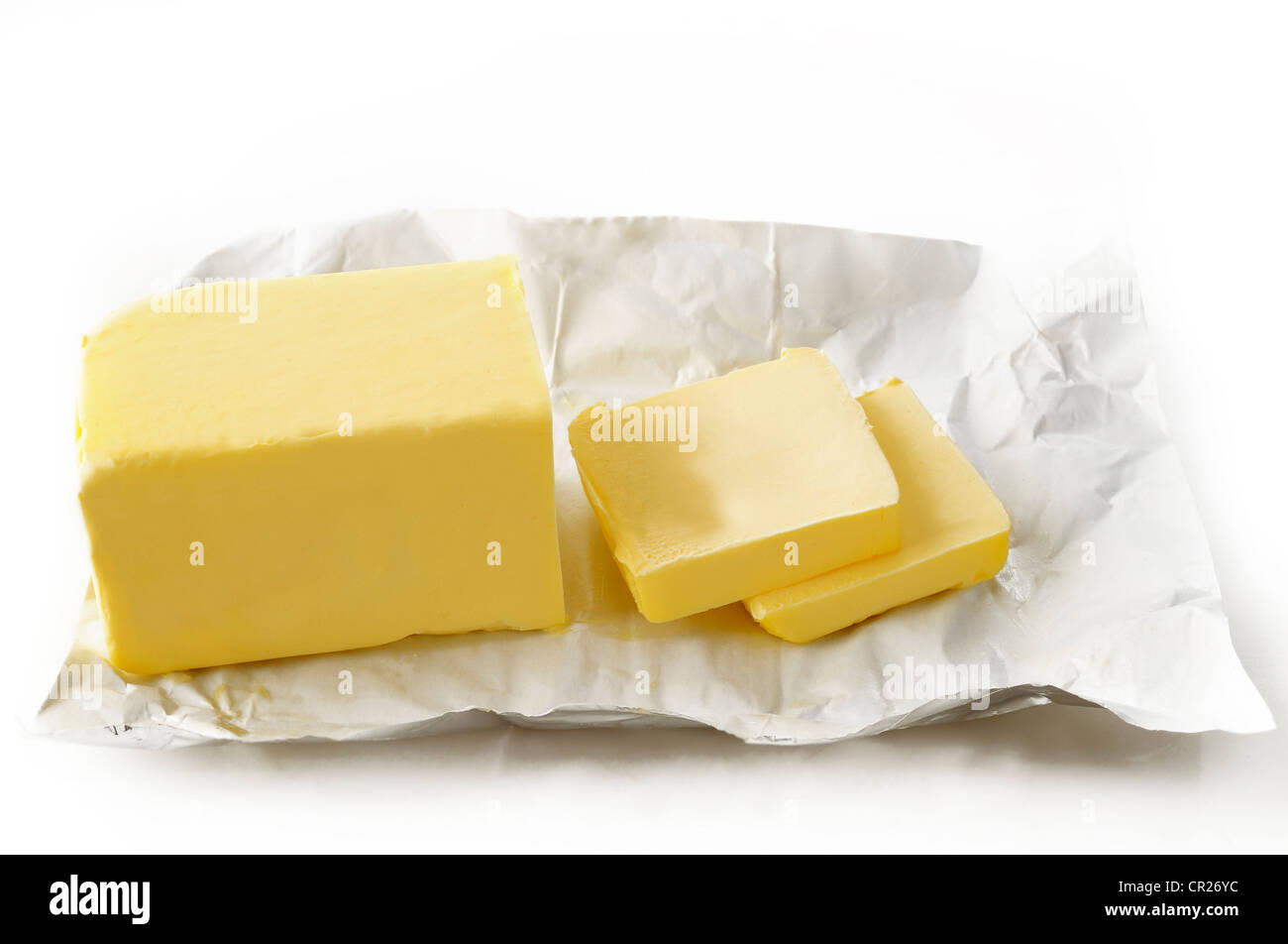 Piece of butter in paper on white background - Stock Image