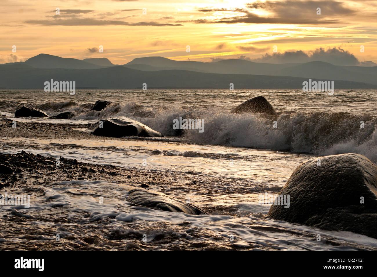 Wave breaks on Criccieth beach as autumn sun rise causes glow over Rhinog mountains - Stock Image