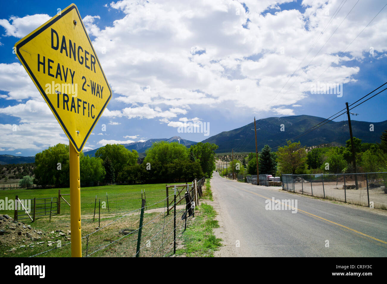 Humorous sign reads 'Danger, Heavy 2-Way Traffic', on rural County Rd 107 near Sallida, Colorado, USA - Stock Image