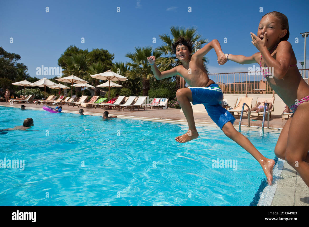 France, Corse du Sud, children jumping into the swimming pool - Stock Image