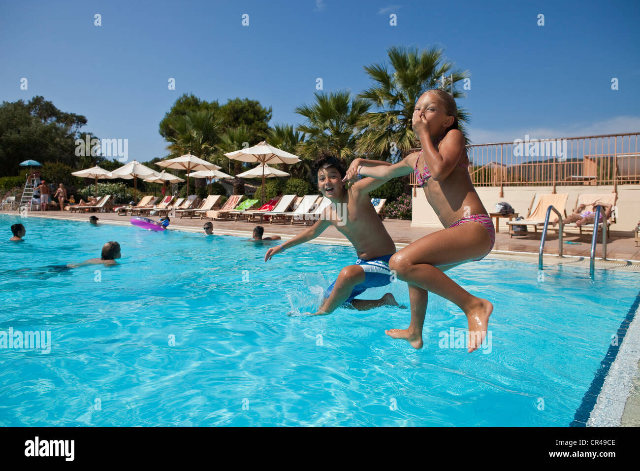 France, Corse-du-Sud, children jumping into the swimming pool - Stock Image