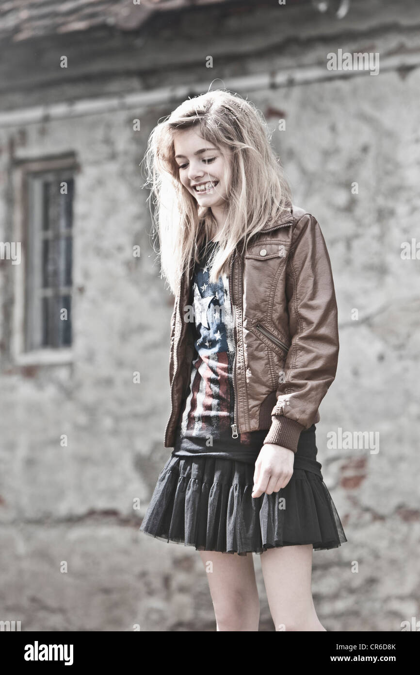 Germany, Bavaria, Girl looking down, smiling - Stock Image