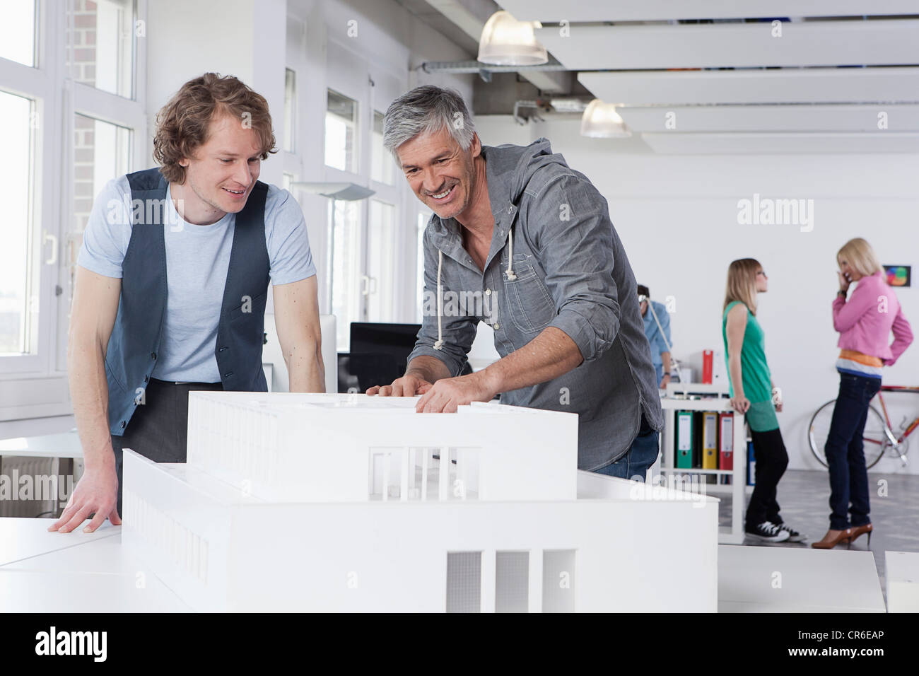 Germany, Bavaria, Munich, Men watching architectural model in office, colleagues talking in background - Stock Image