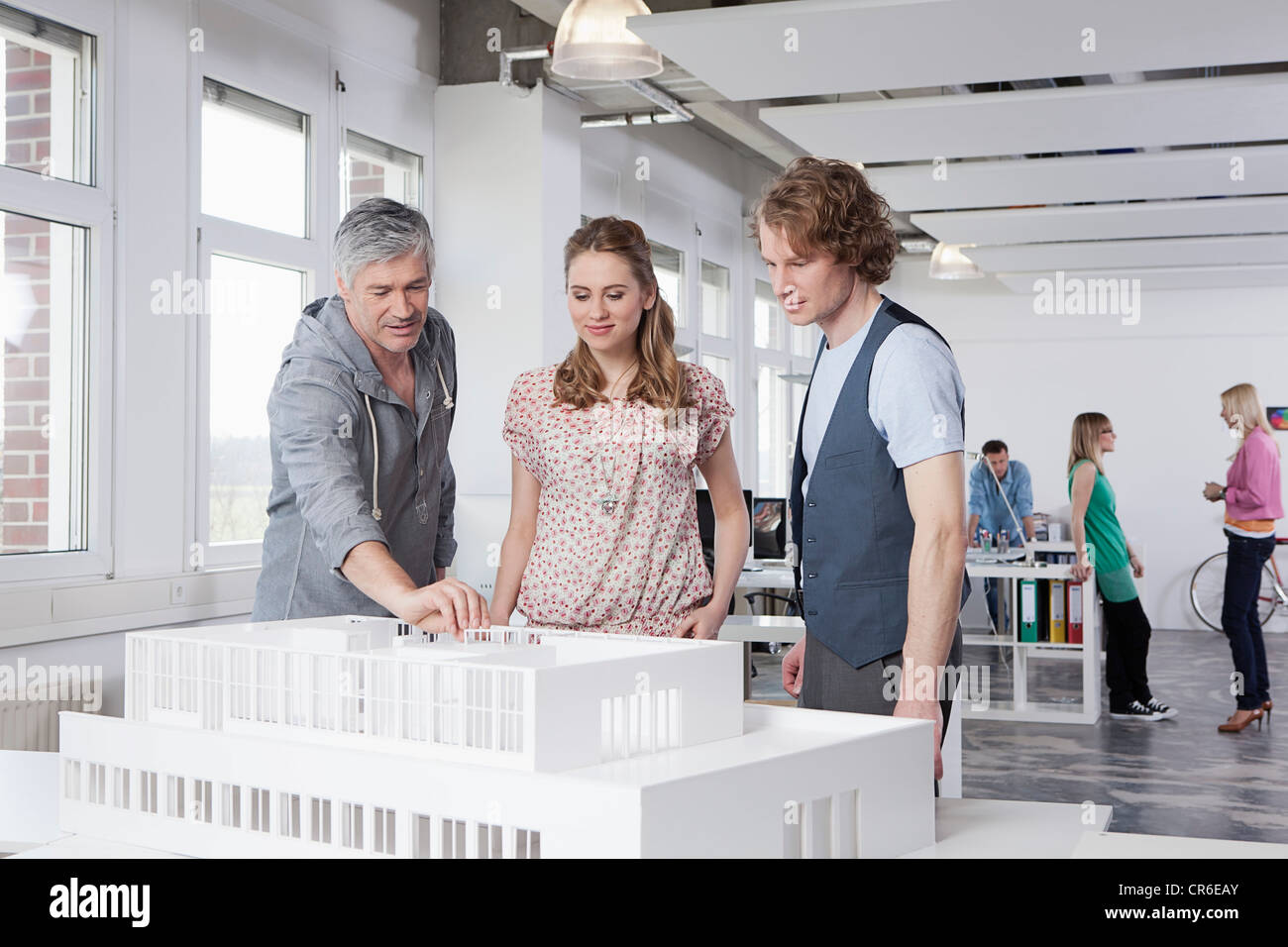 Germany, Bavaria, Munich, Man explaining architectural model to colleagues - Stock Image