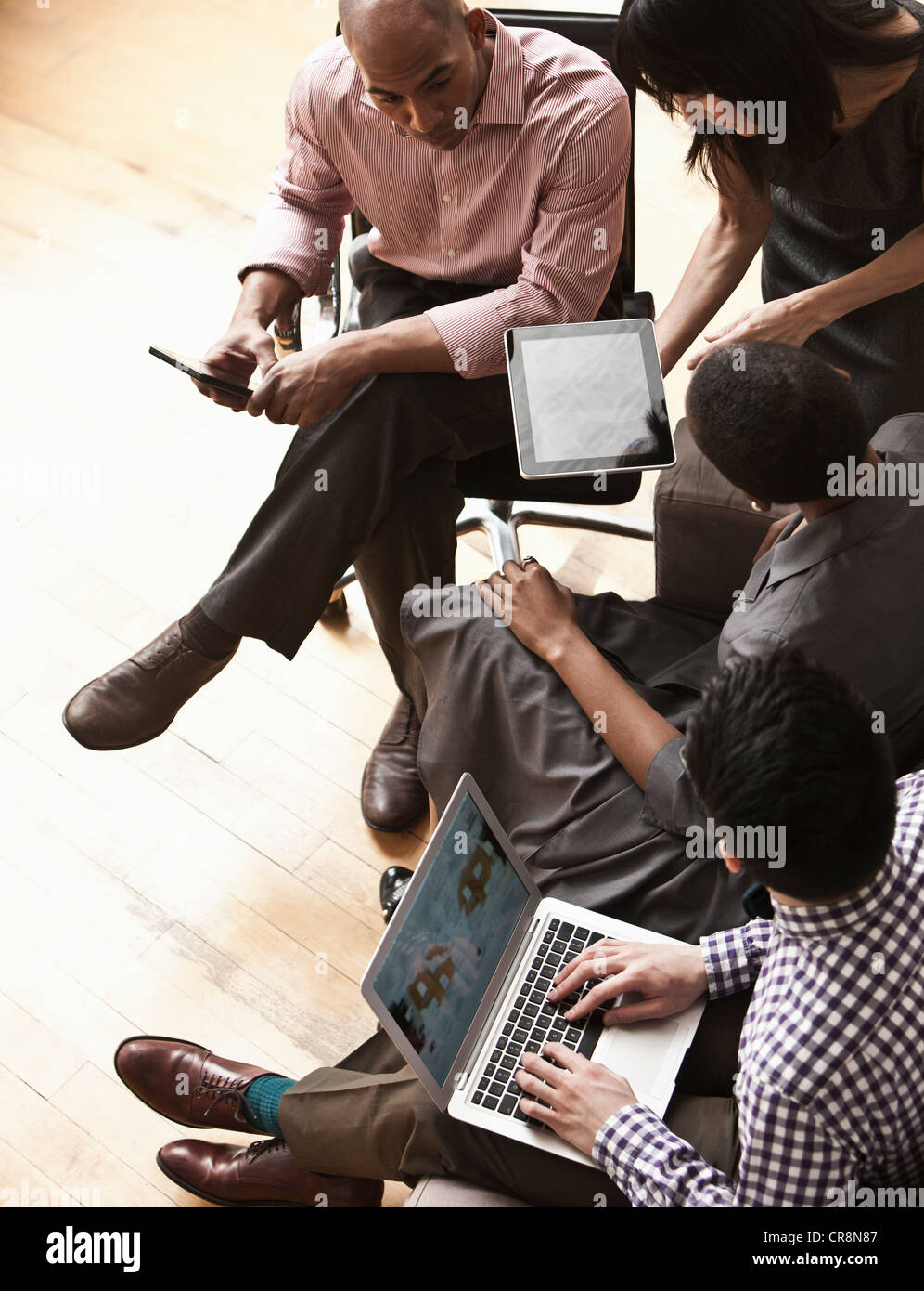 Businesspeople using digital tablet and laptop, high angle - Stock Image