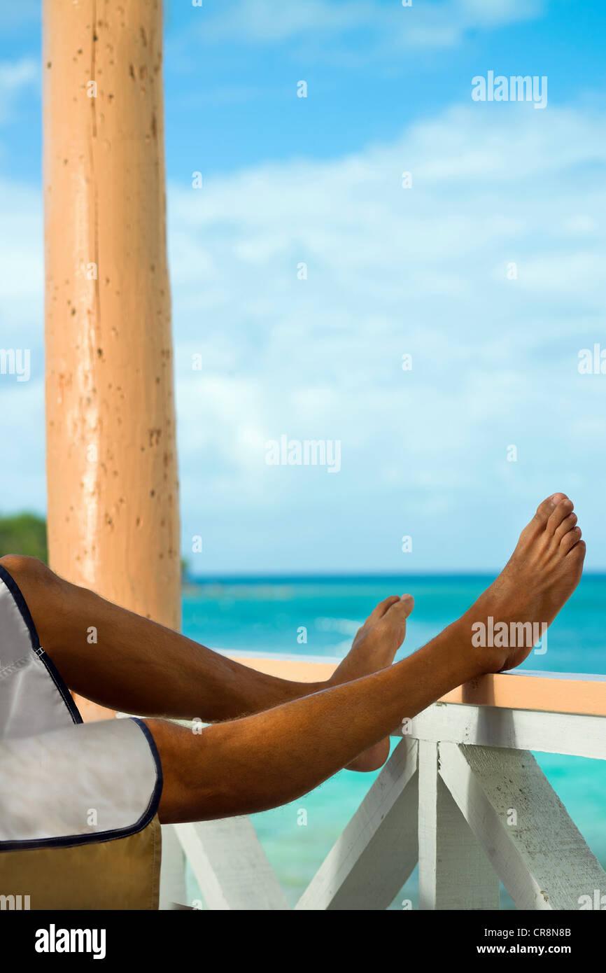 Man on vacation with legs resting on veranda rail - Stock Image