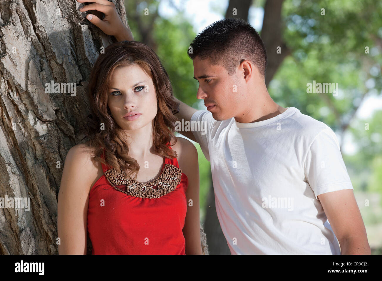Handsome young couple standing in the woods on a bright sunny day, leaning against a tree. Stock Photo
