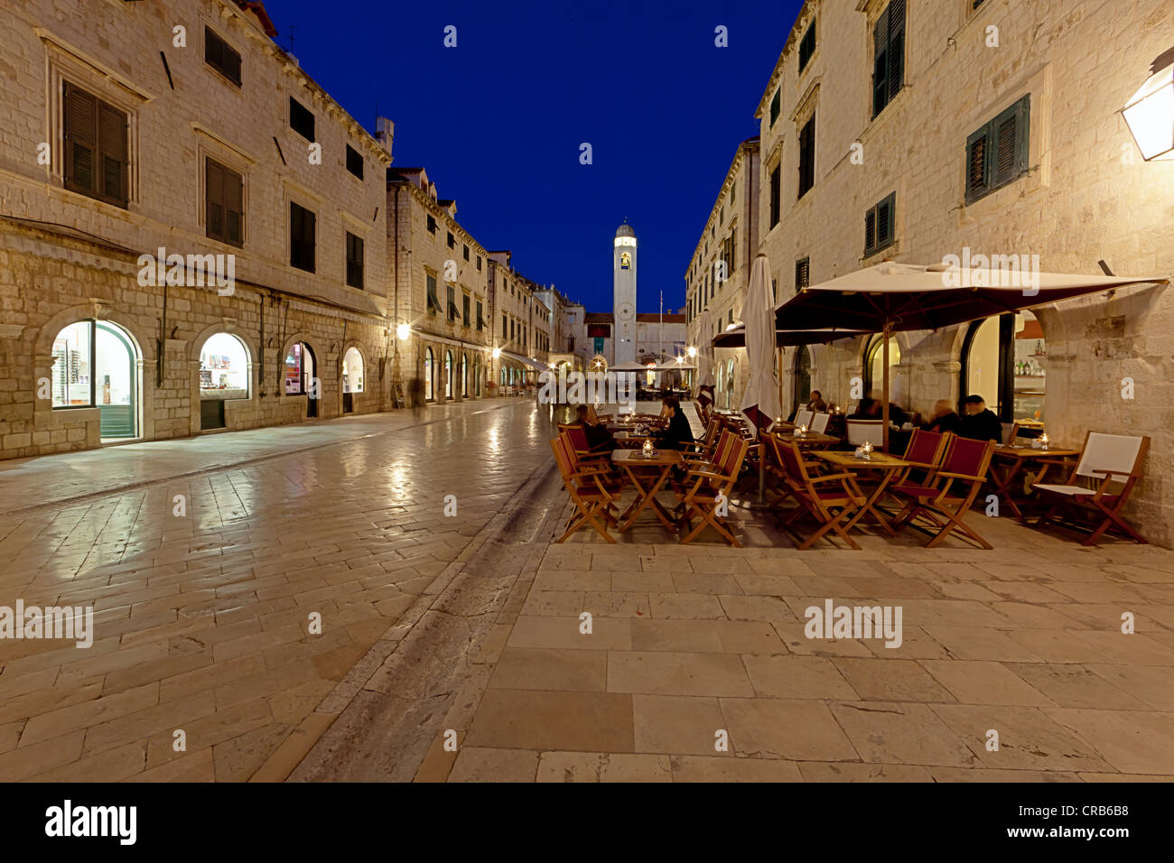 Restaurant in the old town of Dubrovnik at night, UNESCO World Heritage Site, bell tower and Sponza Palace at back - Stock Image
