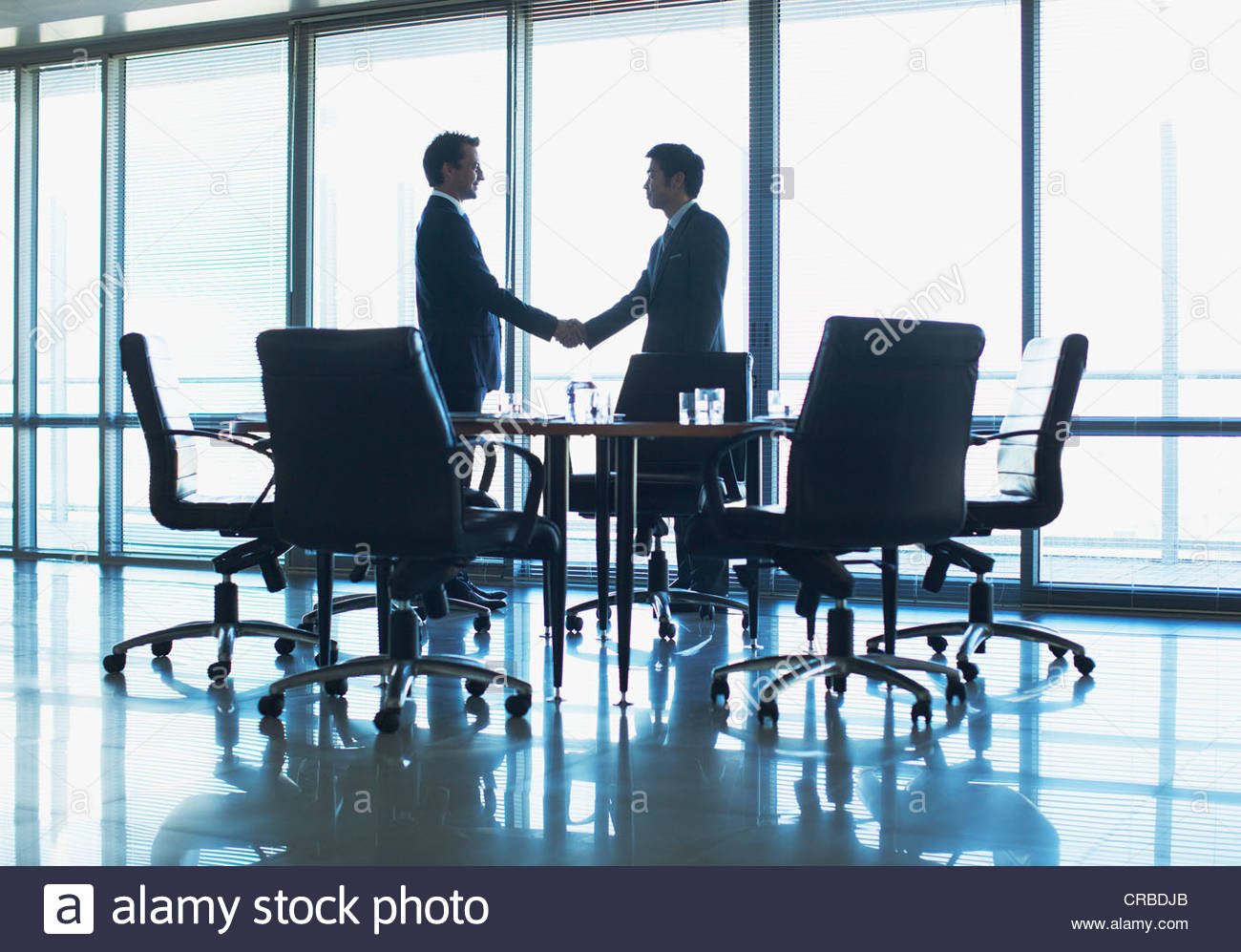 Silhouette of businessmen shaking hands in conference room - Stock Image