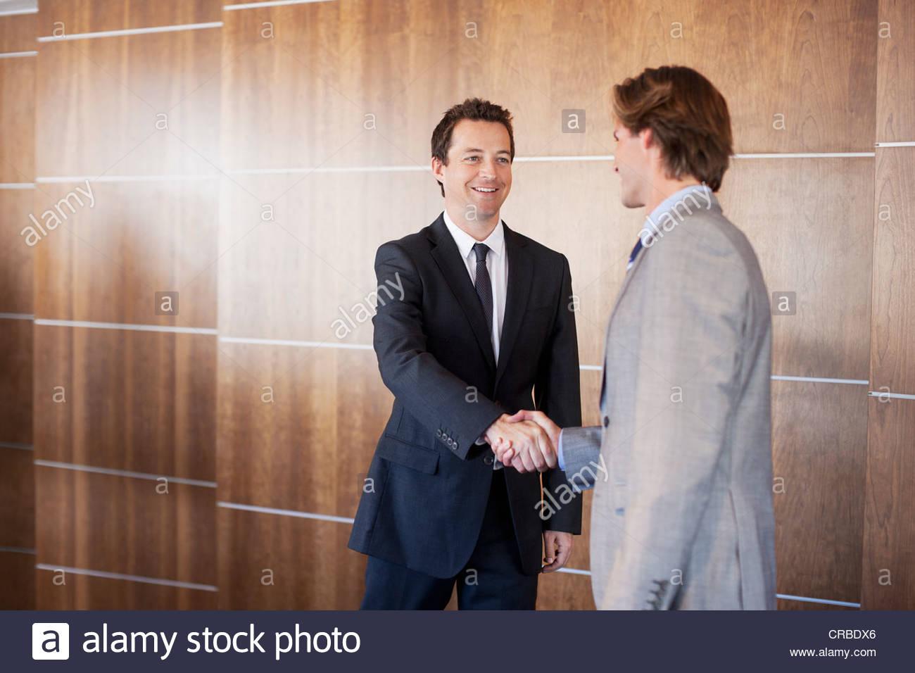 Smiling businessmen shaking hands - Stock Image