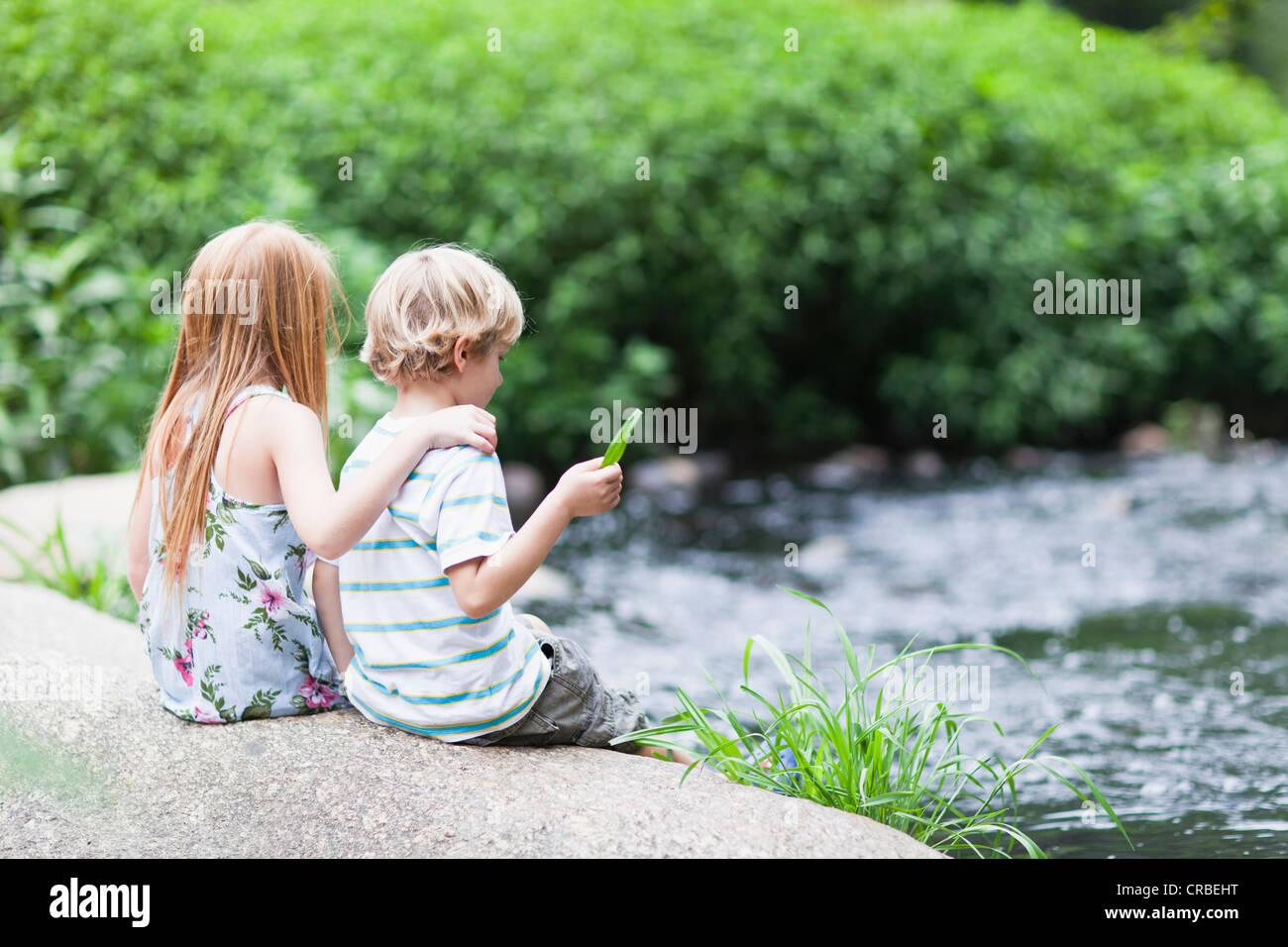 Children sitting on rock together - Stock Image