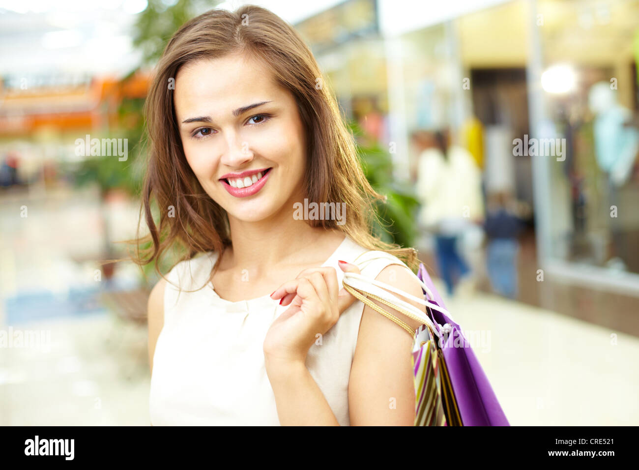 Portrait of a cheerful girl holding a bunch of shopping bags - Stock Image