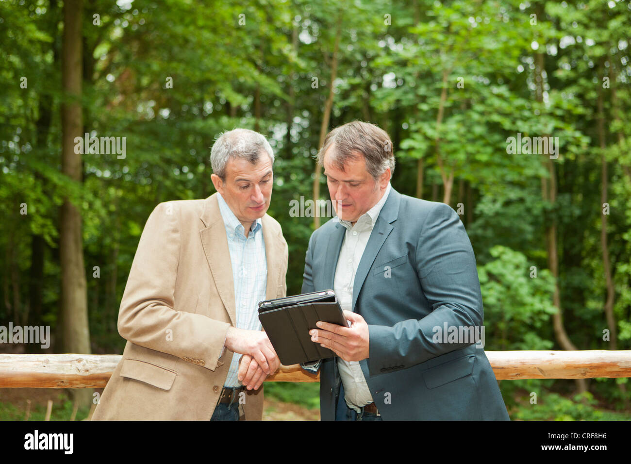 Businessmen using tablet computer - Stock Image