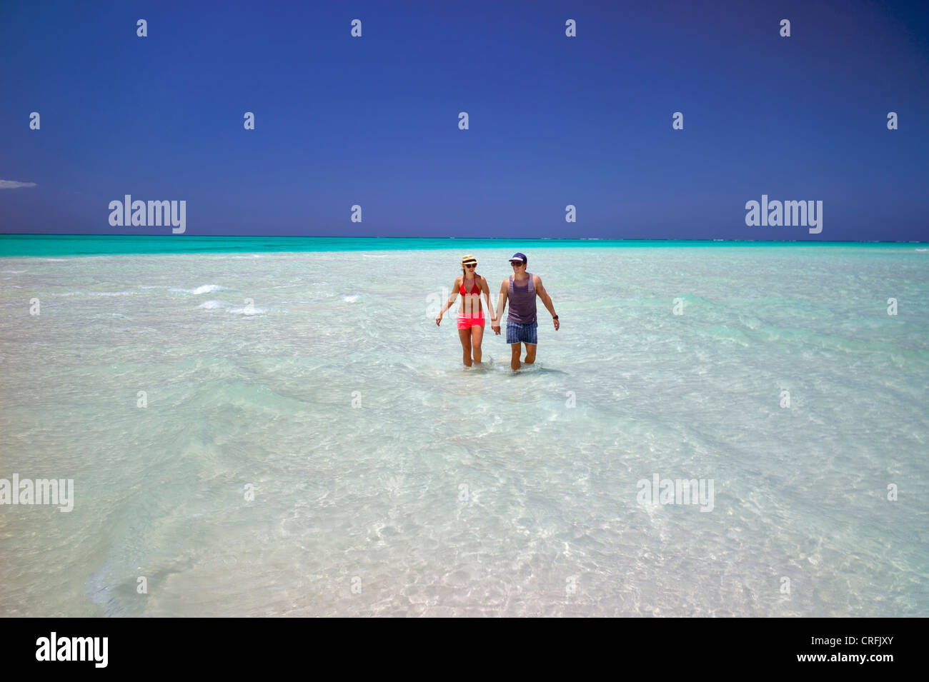 Couple in water of beach of Fort George Cay, an uninhabited island. Turks and Caicos. - Stock Image