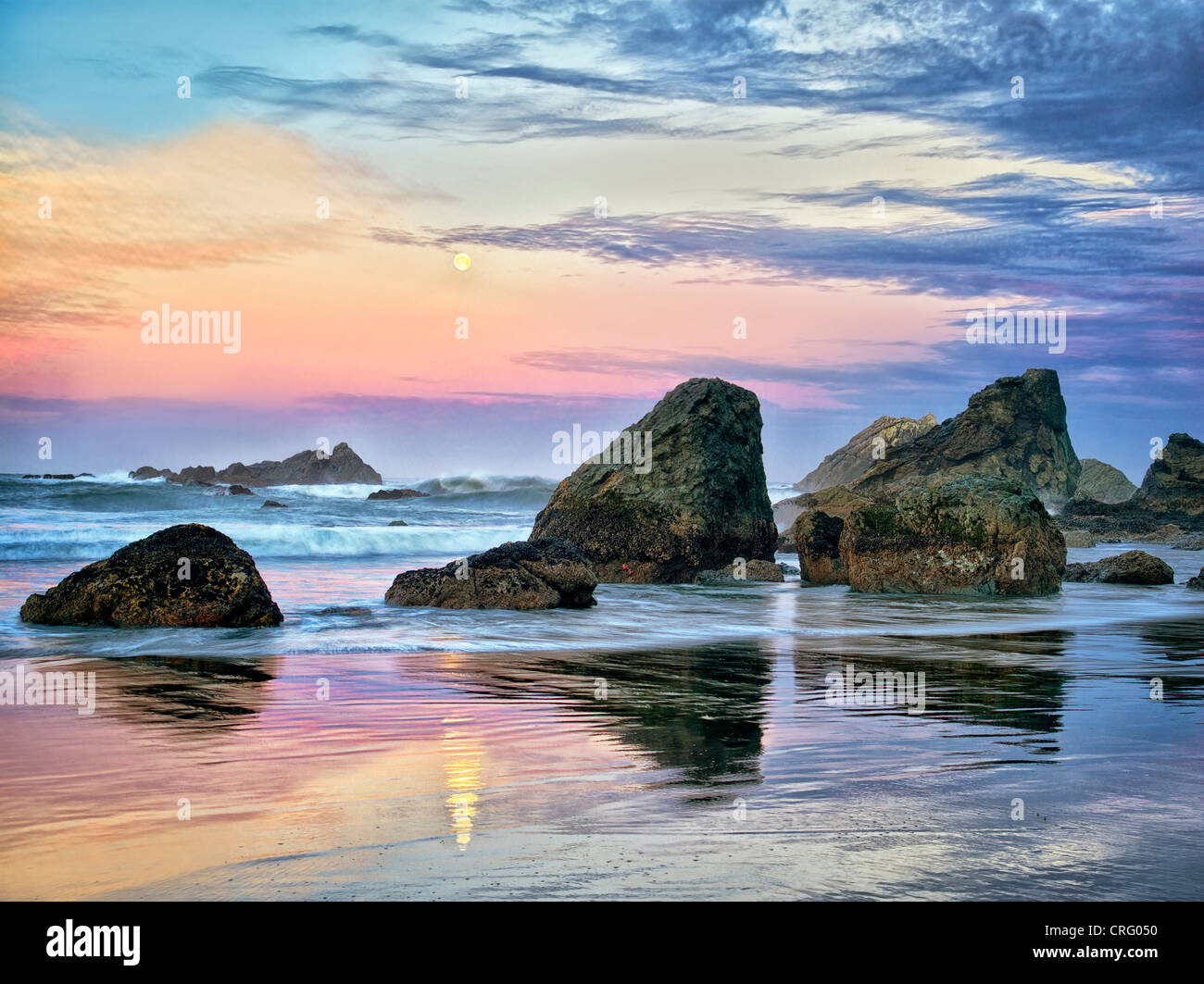 Sunrise and full moonset with reflection at Harris Beach State Park, Oregon - Stock Image