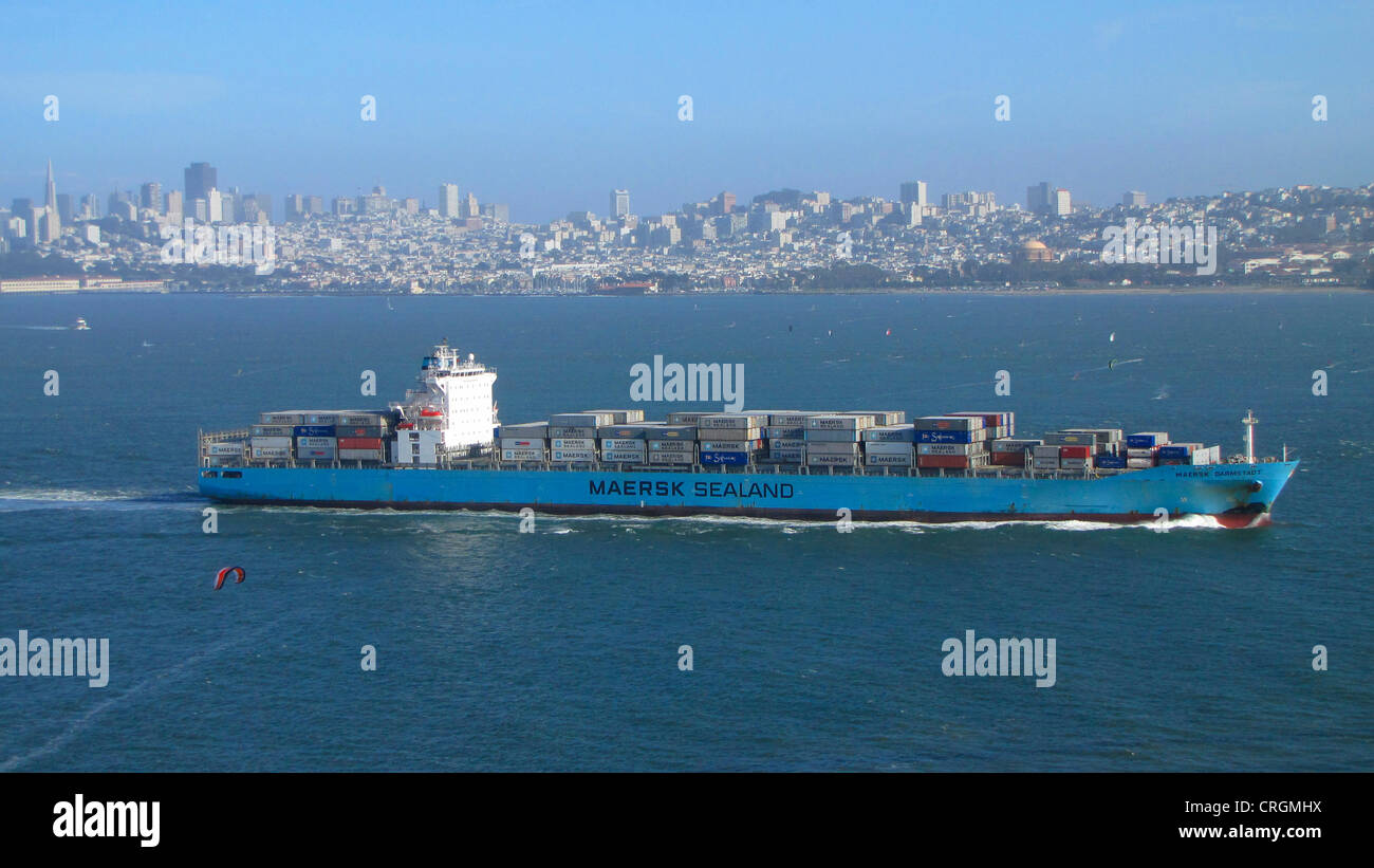 Large cargo ship with freight containers in front of skyline of San Francisco, USA, California, San Francisco - Stock Image