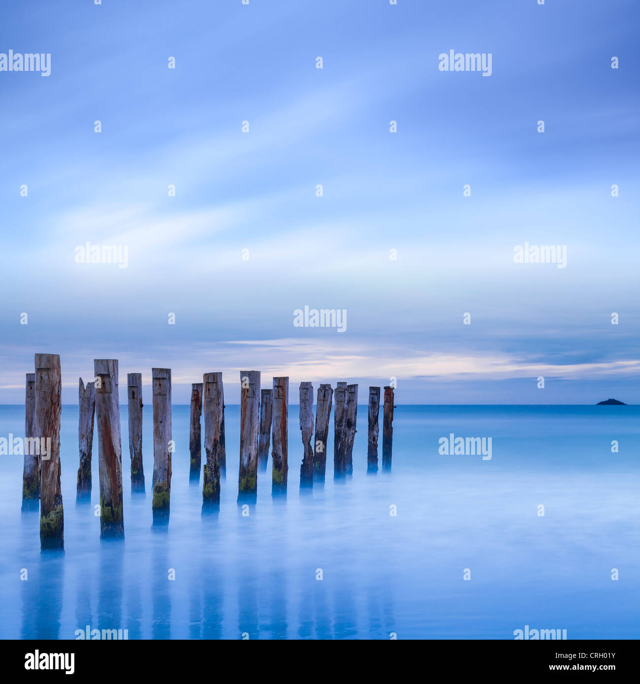 The remains of an old jetty on the beach near Dunedin, New Zealand, just before dawn, square. - Stock Image