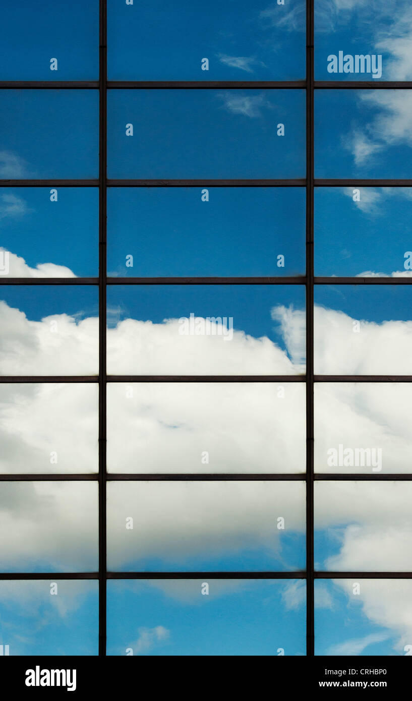 Blue sky and clouds reflected in Office block glass windows. London - Stock Image