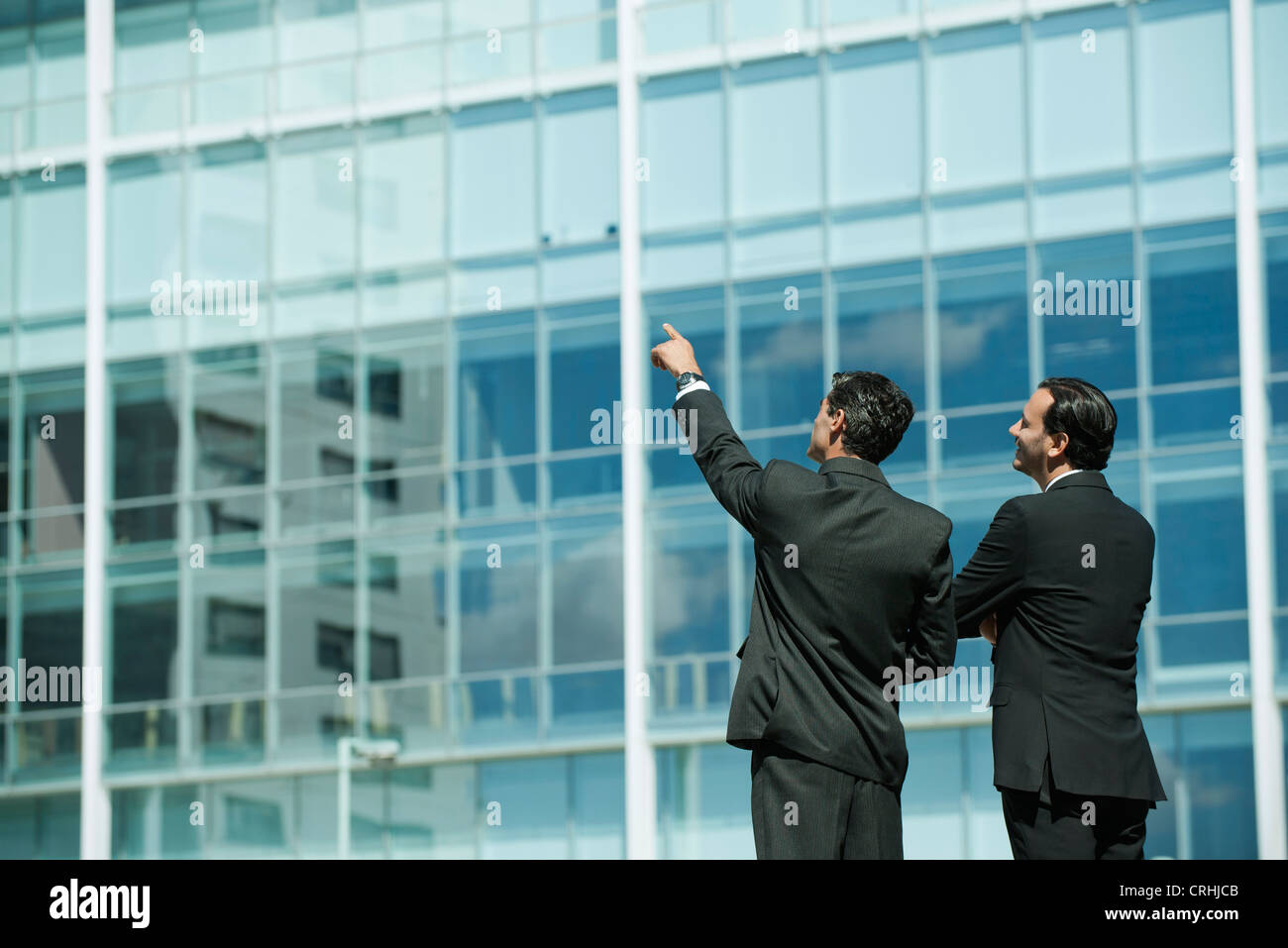 Business executives standing in front of office building, one pointing into distance - Stock Image