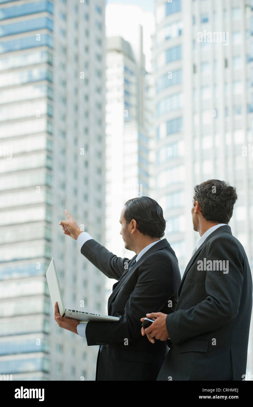 Businessmen using laptop computer outdoors, one man pointing into distance - Stock Image