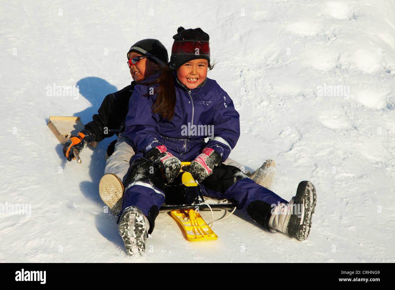children playing in the snow, Greenland, Ostgroenland, Tunu, Kalaallit Nunaat, Scoresbysund, Kangertittivag, Ittoqqortoormiit - Stock Image