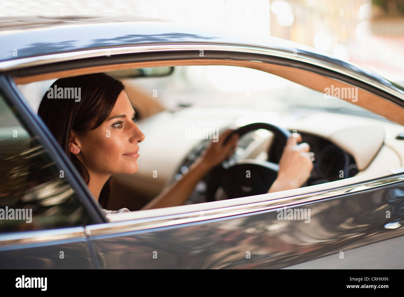 Smiling woman driving sports car - Stock Image