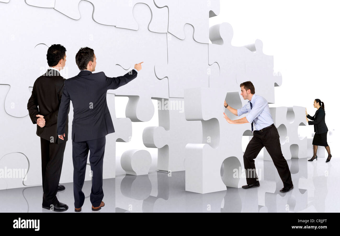 giant puzzle  young business team building a wall of giant puzzle pieces Stock ...