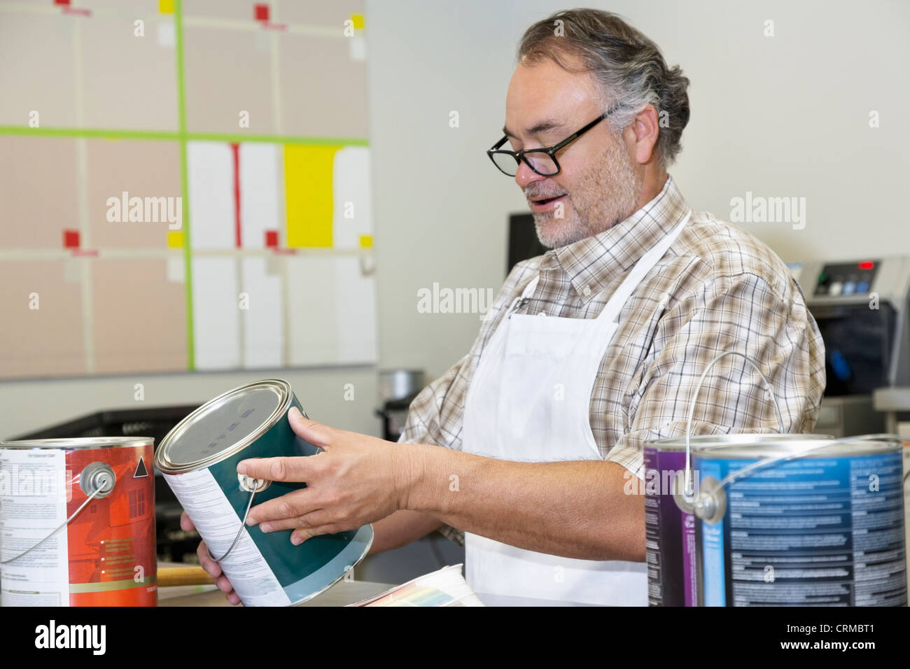 Happy mature sales clerk reading instructions paint can in hardware store - Stock Image