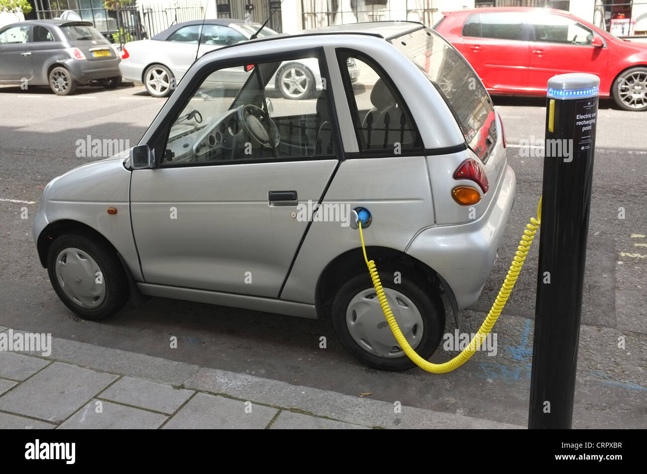A G-Wiz electric car connected to a recharging point in Hinde Street Westminster - Stock Image