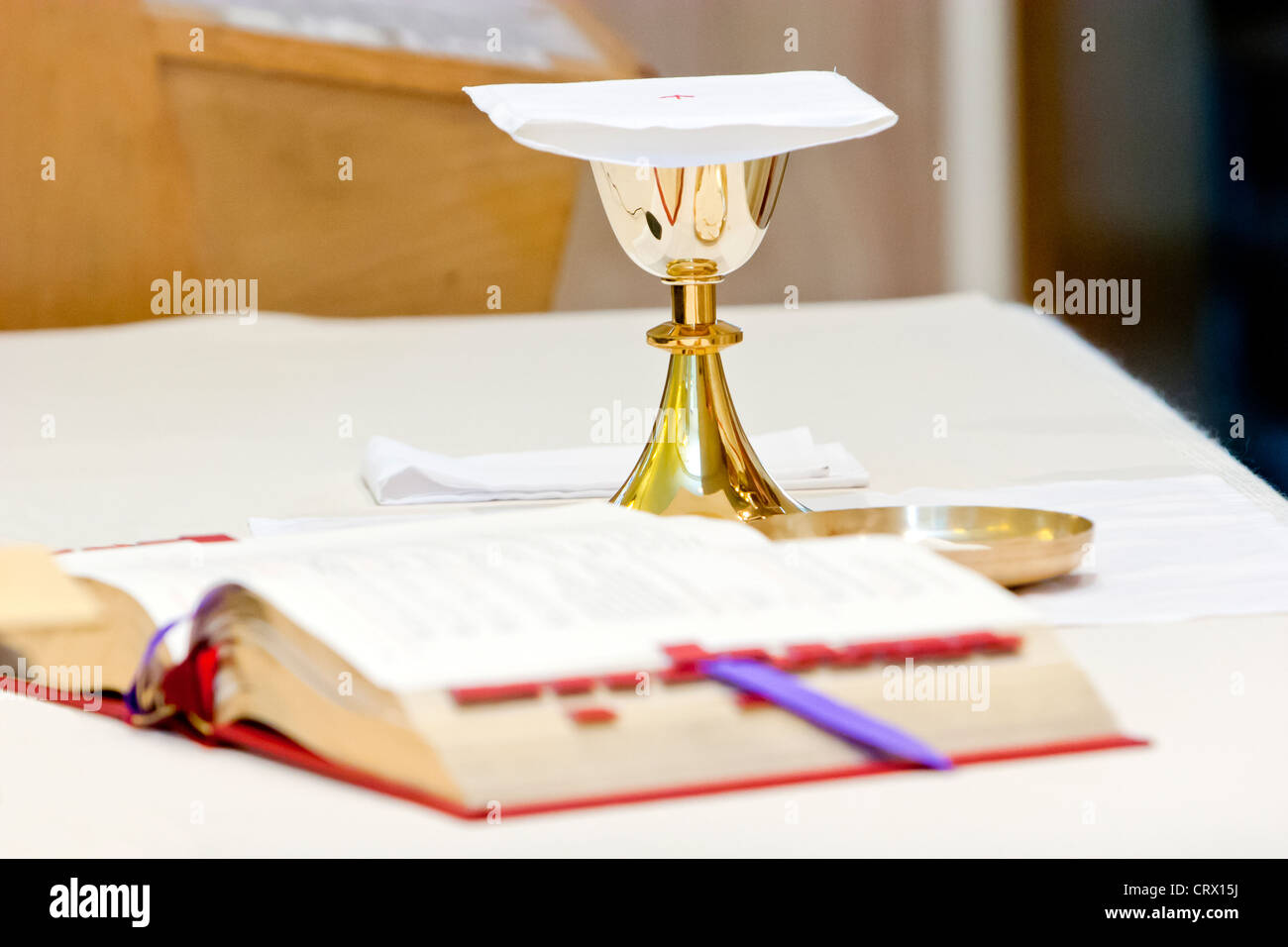 Catholic Mass, a chalice and a prayer book during the religious ceremony. - Stock Image